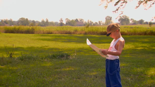 boy looking at poster, farm in background - retro poster stock videos & royalty-free footage