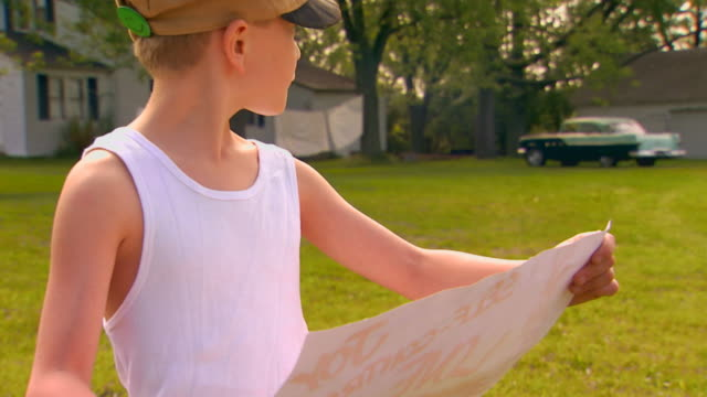 boy looking at poster, looks over his shoulder - retro poster stock videos & royalty-free footage