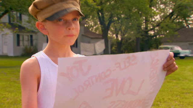 boy looking at poster, looks up and down - retro poster stock videos & royalty-free footage
