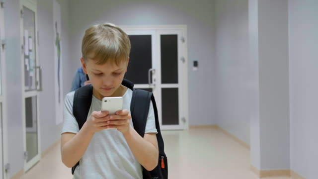 boy looking at smartphone - primary school child stock videos & royalty-free footage