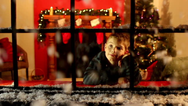 boy looking at snow through window - christmas - christmas stocking stock videos and b-roll footage