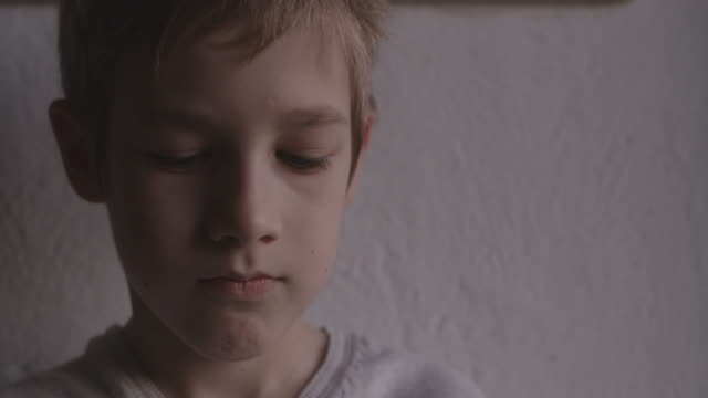 boy looking down - solo un bambino maschio video stock e b–roll