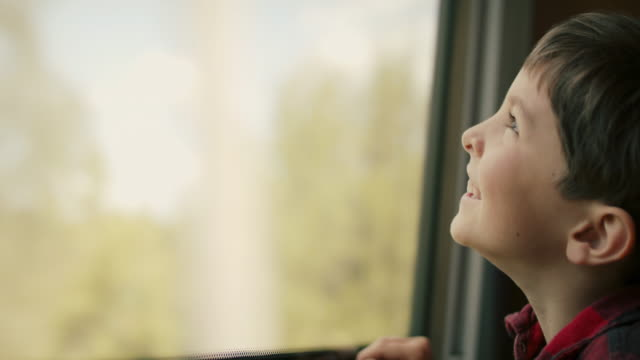 vídeos de stock e filmes b-roll de boy looking out of train window - anticipation