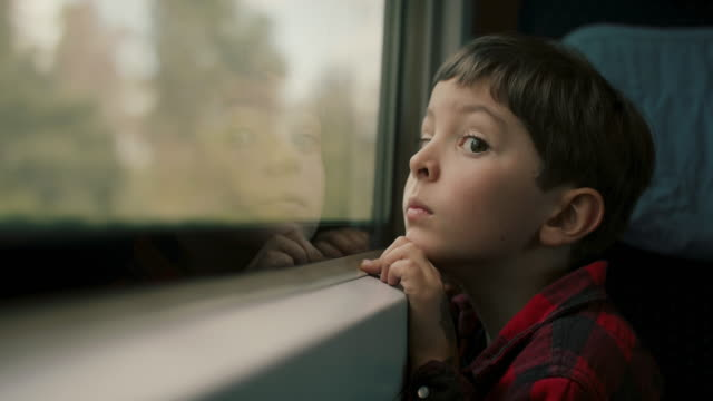 vídeos y material grabado en eventos de stock de boy looking out of train window - anticipation
