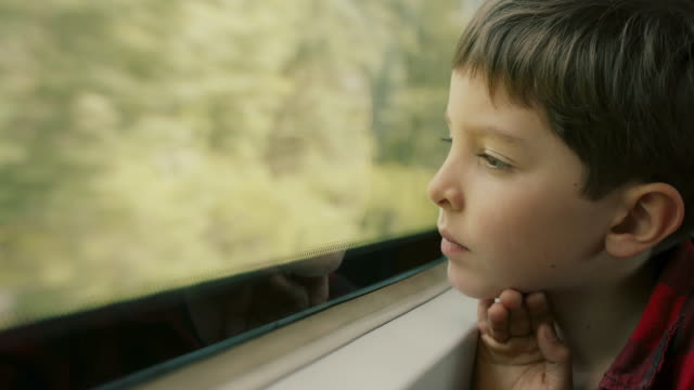 boy looking out of train window - passagier stock-videos und b-roll-filmmaterial