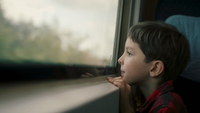 boy looking out of train window - passenger train stock videos & royalty-free footage