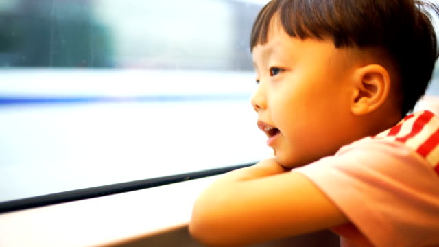 Boy looking out the window at the cars in the metro