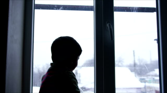 boy looking out the window onto the roof of a neighboring house in the winter - small stock videos & royalty-free footage