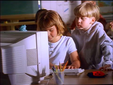 vídeos y material grabado en eventos de stock de boy looking over shoulder of girl typing on keyboard of computer in classroom + smiling - de ascendencia europea