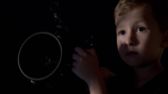 Un garçon regardant à travers un télescope d'astronomie
