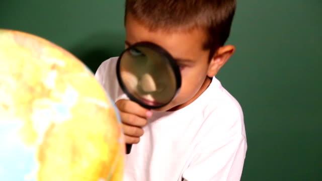 vídeos y material grabado en eventos de stock de niño mirando a través de la lupa en globo - lupa