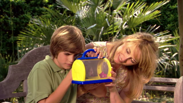 A boy looks at a bug in a small cage with his mother.