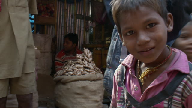 A boy looks at a stranger in the spice market.