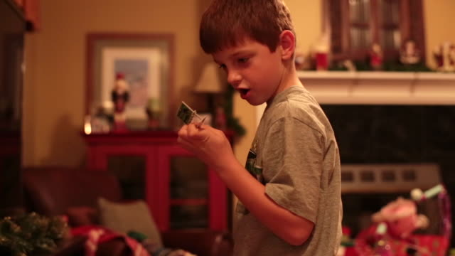 Boy looks at parts and pieces of his train Christmas morning as his train derails
