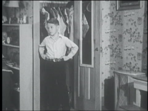 B/W 1950 boy looks out window in bedroom excitedly