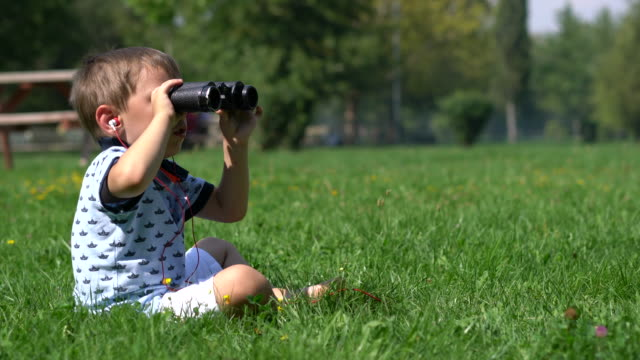 boy looks through the binoculars - looking through an object stock videos & royalty-free footage