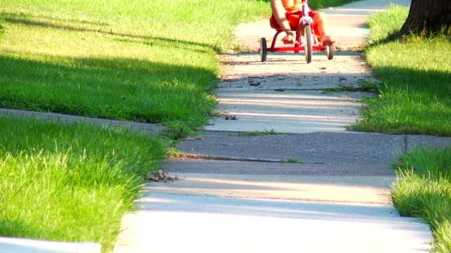 boy low-riding on a tricycle - tricycle stock videos and b-roll footage