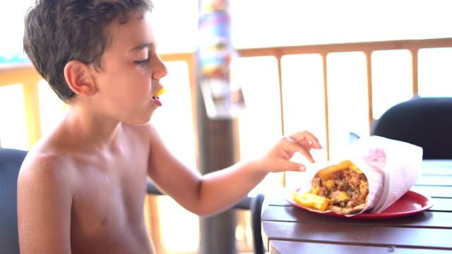 vídeos y material grabado en eventos de stock de niño almuerzo en el restaurante a la playa - sofrito
