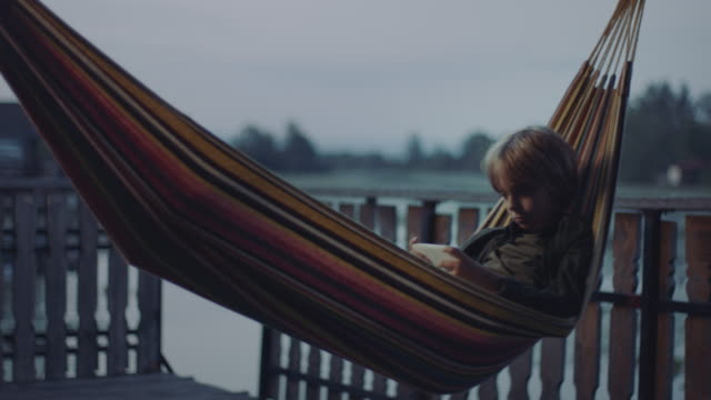 vídeos de stock e filmes b-roll de boy lying down in hammock and playing games on smartphone - cama de rede