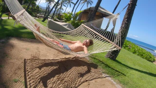 vídeos de stock e filmes b-roll de a boy lying in a hammock at beach in kaanapali, maui, hawaii. - slow motion - napping