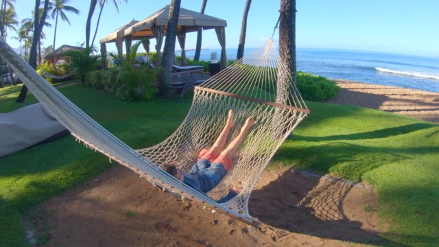 vidéos et rushes de a boy lying in a hammock at beach in kaanapali, maui, hawaii. - napping