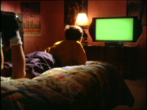 vidéos et rushes de boy lying on bed playing video game (blank screen) - écran blanc