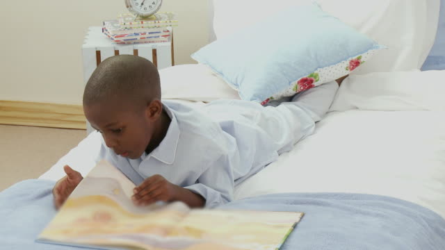 WS PAN Boy (4-5) lying on bed reading book / Cape Town, South Africa