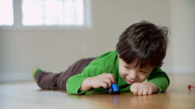 CU, Boy (2-3) lying on floor and playing with toy car, Plainfield, New Jersey, USA
