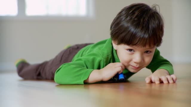 cu, boy (2-3) lying on floor and playing with toy car, plainfield, new jersey, usa - 男児1人点の映像素材/bロール