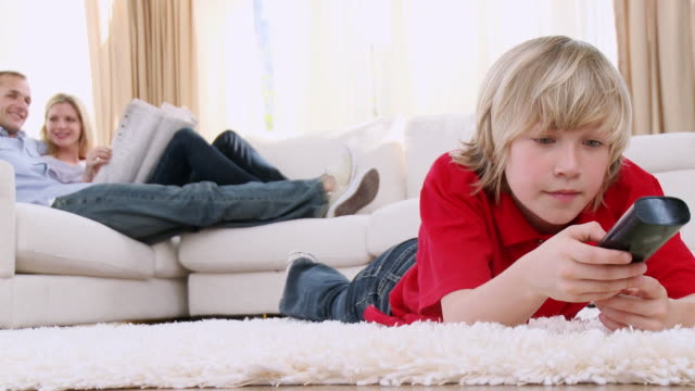 ms boy (8-9) lying on floor with remote control, parents in background / cape town, south africa - mid length hair stock videos & royalty-free footage
