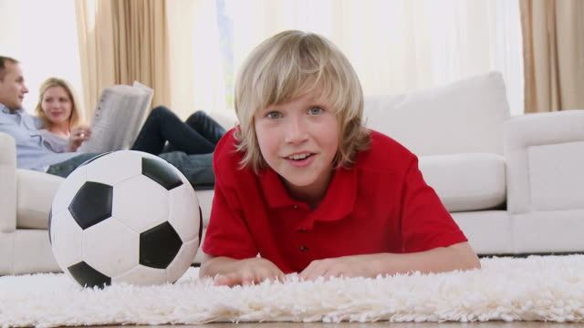ws boy (8-9) lying on floor with soccer ball watching tv / cape town, south africa - see other clips from this shoot 1811 stock videos & royalty-free footage