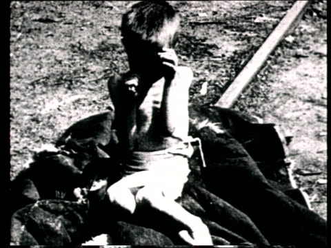 1925 MONTAGE B/W MS Boy lying on front and eating food from ground during Russian famine/ MS Emaciated boy crying/ MS Bodies lying on ground in the aftermath of famine and catastrophe/ WS PAN Bodies piled in graveyard in the aftermath of famine/ Russia