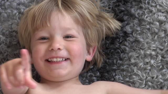 cu slo mo boy (2-3) lying on rug, smiling / gavle, gavleborg county, sweden - 2歳から3歳点の映像素材/bロール