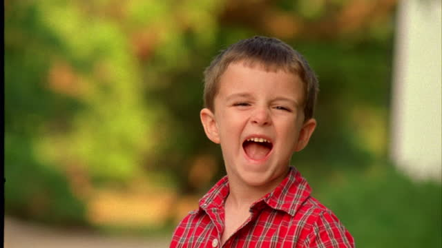 vídeos de stock, filmes e b-roll de a boy makes a face and smiles. - olhos castanhos