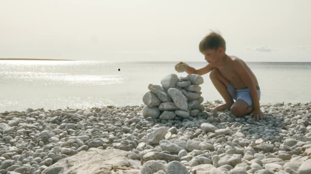 boy making a pile of white rocks at the beach on a sunny day - crouching stock videos and b-roll footage