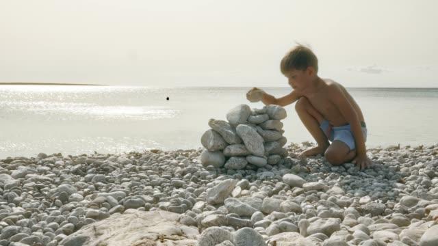 vídeos de stock, filmes e b-roll de rapaz, fazendo um monte de pedras brancas na praia em um dia ensolarado - tronco nu