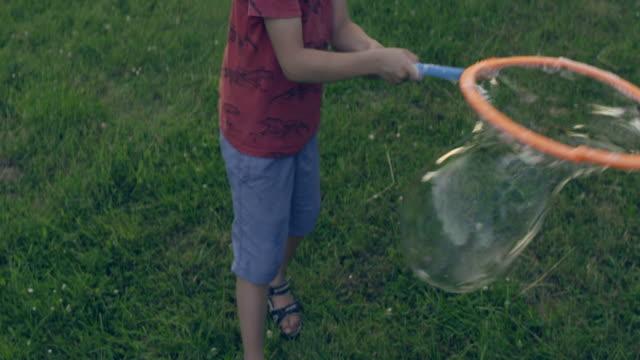 公園で泡を作る少年。夏の楽しみ - 大きい点の映像素材/bロール