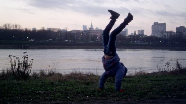 boy making cartwheel on a riverside. cityscape in background. sunset - cartwheel stock videos & royalty-free footage