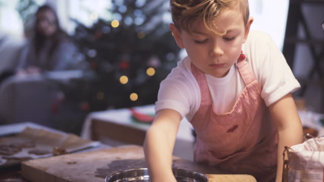 Boy making Christmas cookie with family