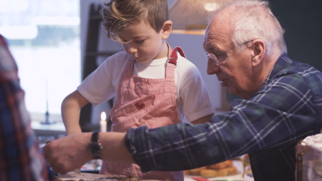 vídeos de stock, filmes e b-roll de boy making christmas cookie with grandfather - 65 69 anos