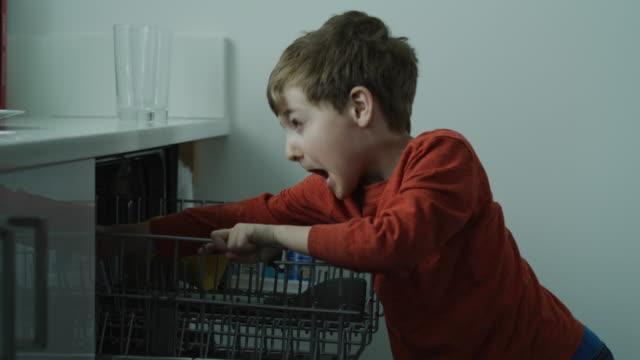 boy making faces while unloading dishwasher / lehi, utah, united states - lehi stock videos & royalty-free footage