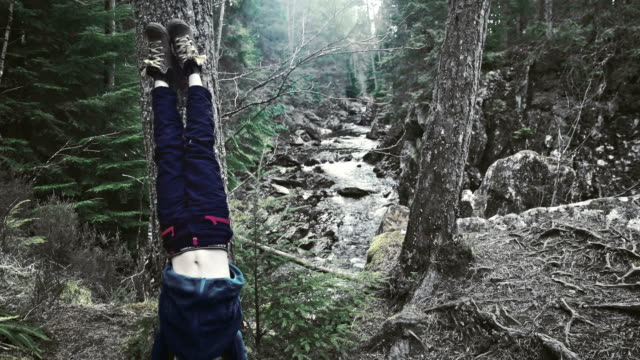 Boy making headstand in mountain ravine. Rocks covered with moss and brake