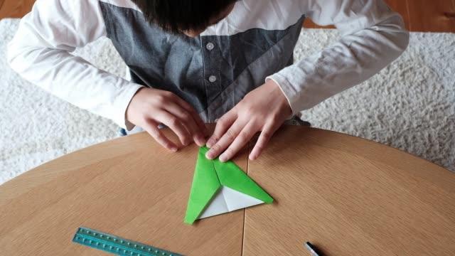 vidéos et rushes de boy making paper plane - origami