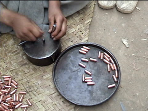 boy manually making bullets in middle of street, darrah district in tribal zone at afghan border, federally administered tribal areas, pakistan, audio - 男児のみ点の映像素材/bロール