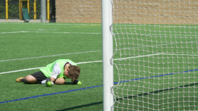a boy missing a goal gets angry youth soccer football goalie goalkeeper on a turf grass field wearing green. - slow motion - image focus technique stock videos & royalty-free footage