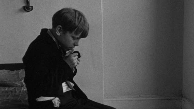 1976 b/w boy mourning the death of his father and wiping his nose on his jacket / liverpool, merseyside, england - grief stock videos & royalty-free footage