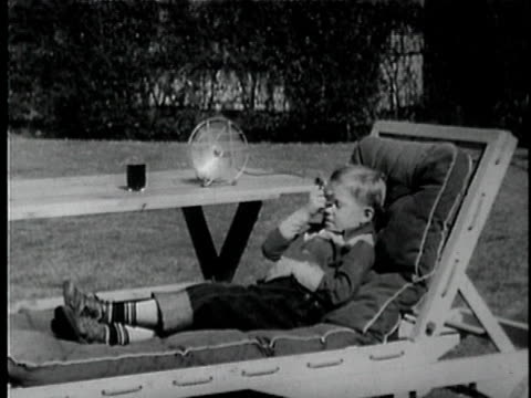 MONTAGE B/W WS MS Boy napping on lounge chair and wiping his forehead with handkerchief while electric fan blows on him / Los Angeles, California, USA