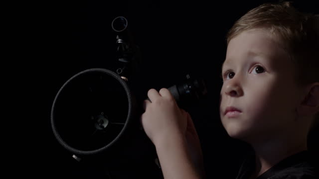 boy observing the night sky - looking through an object stock videos and b-roll footage