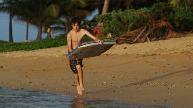 vídeos de stock e filmes b-roll de boy on a bodyboard - só um menino adolescente