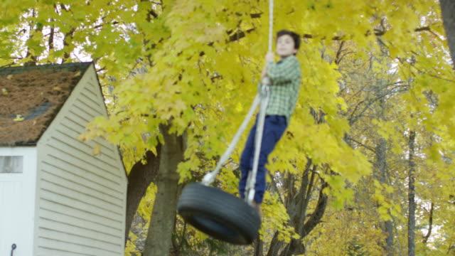 vidéos et rushes de a boy on a rope swing - balançoire pneu